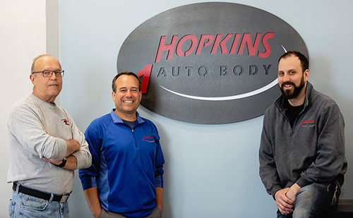 Front of sign about Hopkins Auto Body